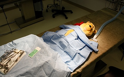 A stuffed animal under the light on the surgery table