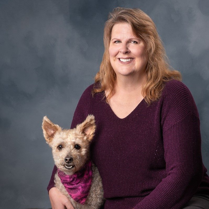 http://A%20woman%20in%20purple%20sweater%20holding%20a%20dog