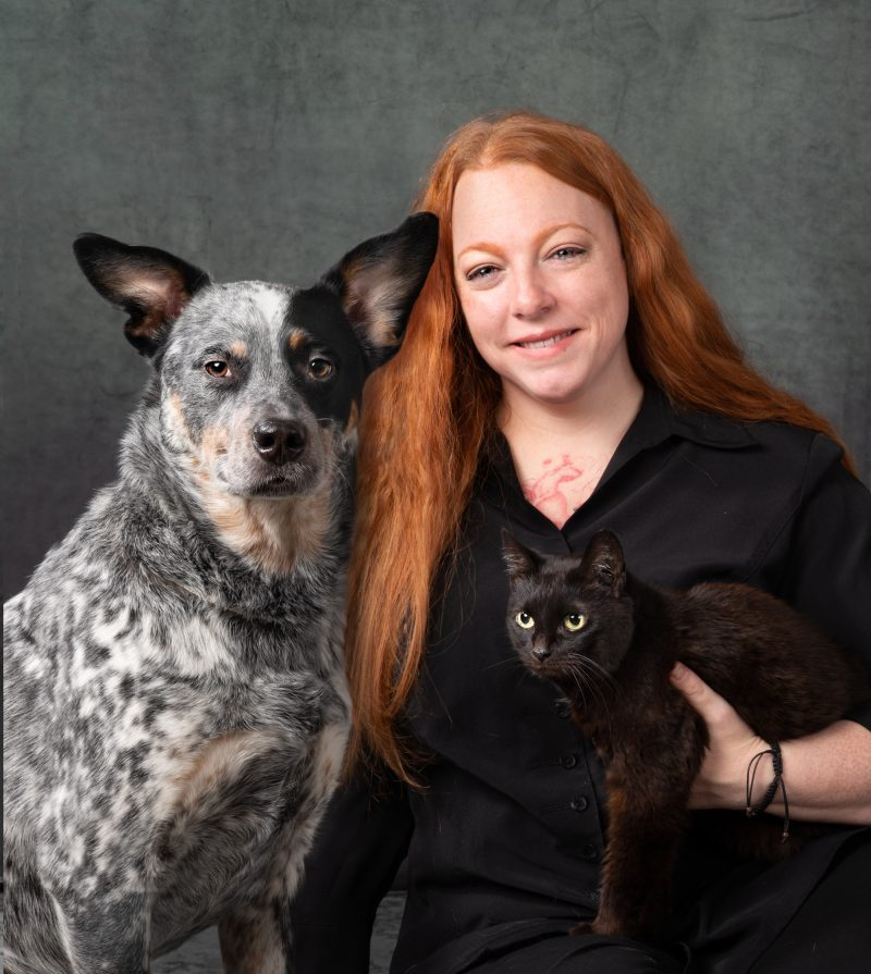 http://Red%20haired%20woman%20wearing%20black%20top%20holding%20a%20black%20cat%20and%20a%20tricolored%20dog%20sitting%20besides%20her.